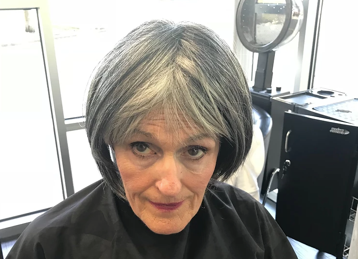 Woman trying on a wig to see if she likes herself with grey hair