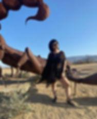 Lauren Bielma standing in front of a metal scorpion in the desert