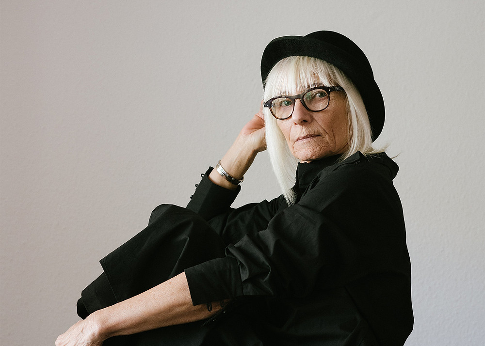 Sophisticated woman with grey shoulder length hair, black hat and black glasses