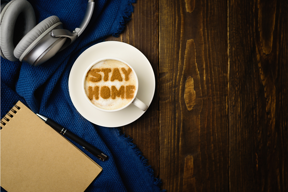 "Top of foamy latte cup with ""STAY HOME"" written in cinnamon"