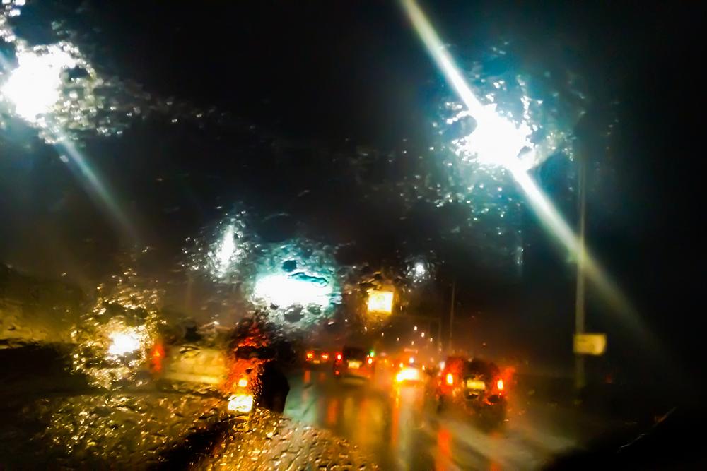 Rainy night on a freeway through a windshield