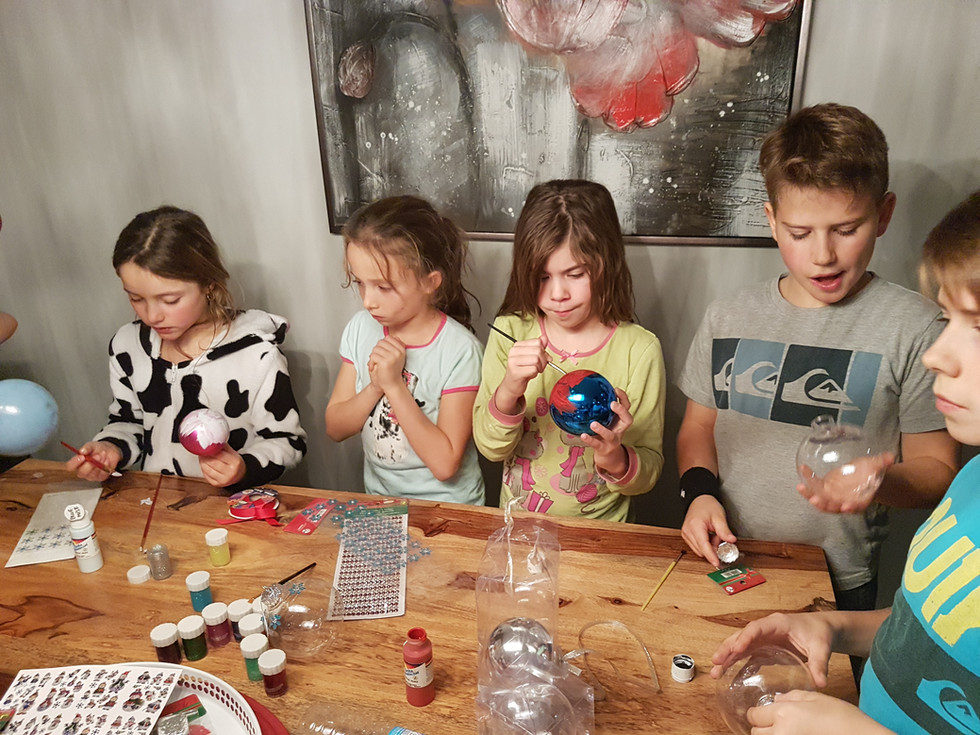 Children in the process of making Christmas decorations.