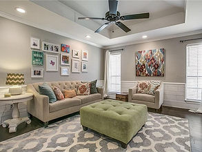 Tufted beige couch with matching chair, green ottoman, and bright accent decor