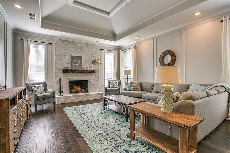 Light gray living room with gray couch, blue and green accents, and a limewashed white fireplace
