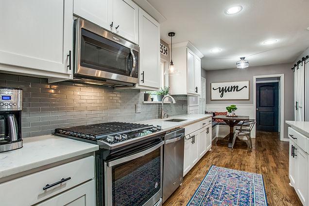 White kitchen cabinets, black hardware, gray backsplash, and built-in kitchen nook