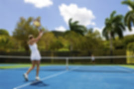 Healthy man and woman playing tennis near palm trees