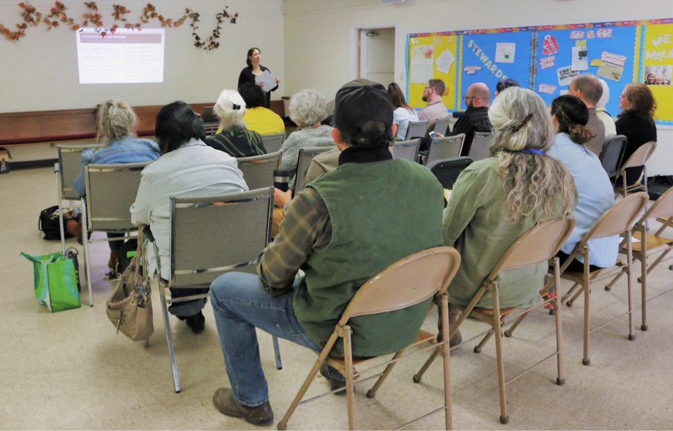 A group of people sit listening to a presentation on tenants' rights.