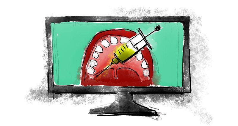 Una inyectadora que apunta a una boca abierta en una pantalla de computadora. Representación de la enseñanza de disciplinas prácticas como la odontología a través de medios virtuales.