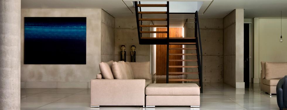 Foto casa estilo moderno minimalista com escada ao fundo e um sofá no primeiro plano.