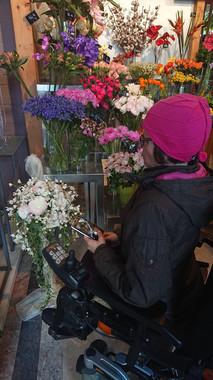Ogleduje si rože, saj jih ima zelo rada.  Tina, in her scarf, is observing animals by the Ljubljanica River.