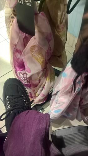 V trgovini izbiram ter ogledujem zbirko šalov.  At the store picking and browsing a selection of scarves.