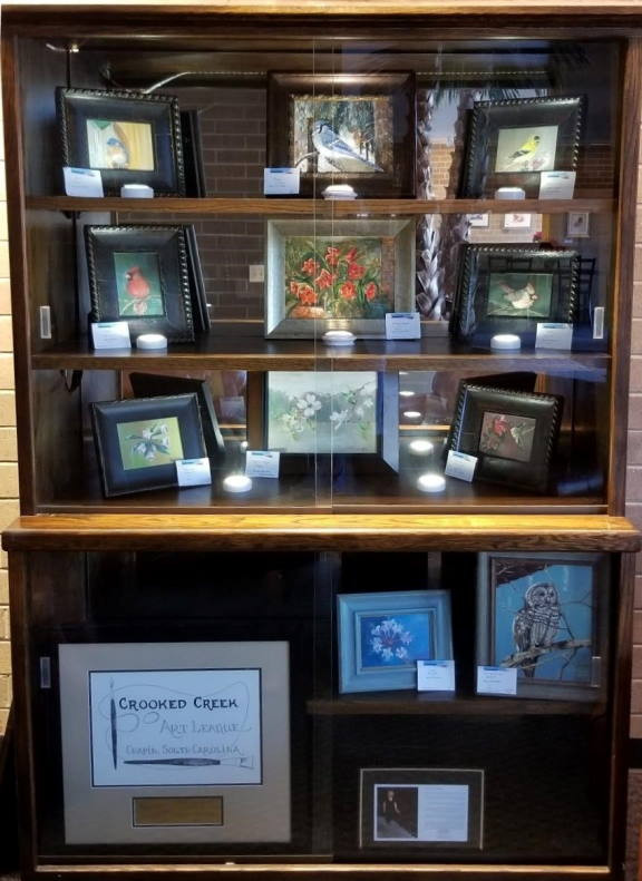 Photo of filled display cabinet with Mary Williams artwork