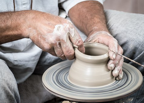 Hands of a potter working on clay on a pottery wheel