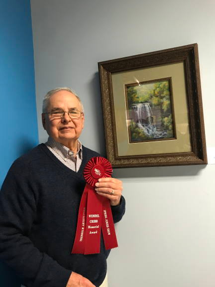 """Photo of artist Al Leitch with his awarded painting """"Dry Falls"""""""