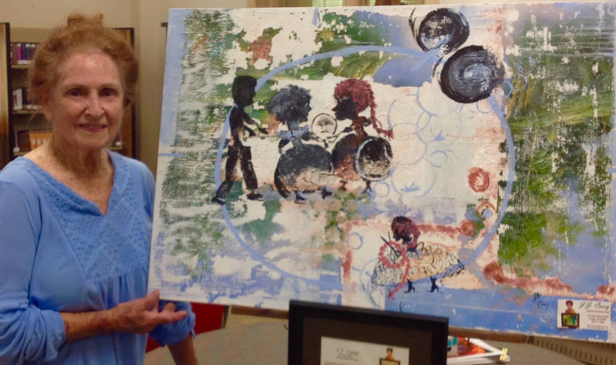 """Photo of artist JJ Casey with painting """"Family Circle"""""""
