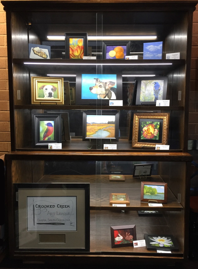 Photo of filled display cabinet with Barbara Teusink's original oil paintings