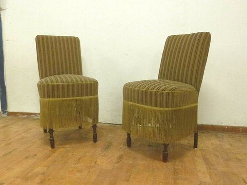 A pair of Danish lounge chairs with green velour upholstery.