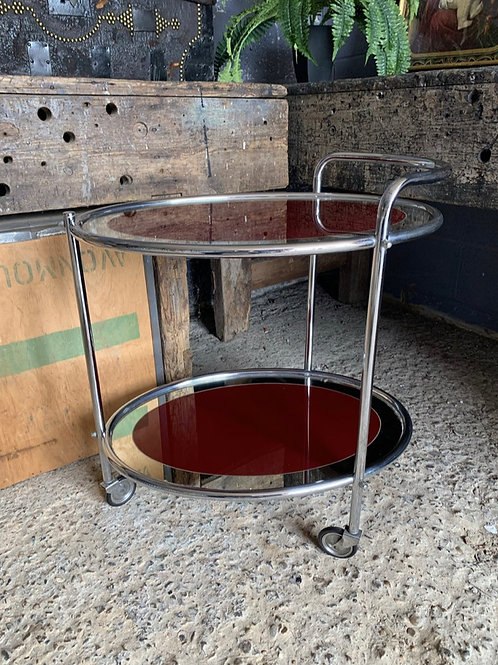 An Art Deco two-tier drinks trolley with red glass on castors