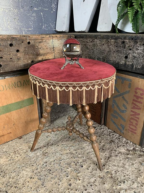 A wooden bobbin gypsy table with red velvet top