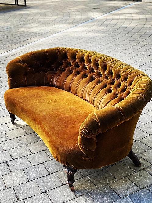 A 19th century kidney shaped sofa raised on turned legs
