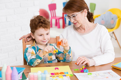 Little happy boy having classes with occupational therapist. Setting words from colorful l