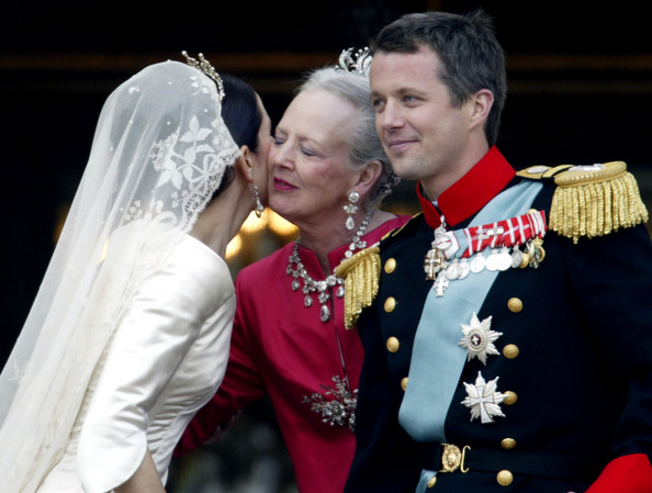 Mary Donaldson (now the Crown Princess of Denmark) kisses the Queen on the cheek. The Queen and Prince Frederick are both facing the camera all decked out in jewels and medals, but Mary is facing the other way, her face mostly concealed by the Queen. She is identifiable only by her wedding veil