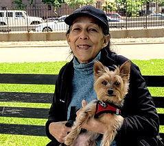 New York's Pet Pal dogwalker Anneris smiles and sits on a bench in East River Park while hugging Max, a tan yorkshire terrier.
