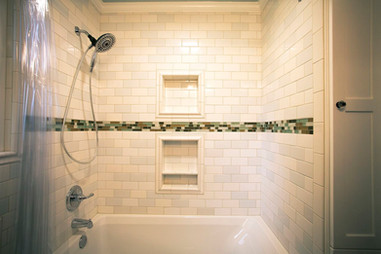 The tub surround got some extra storage with two niches and was tiled with a blend of three different white subway tiles and beachy glass accents.