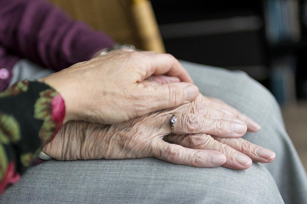 holding a senior's hand