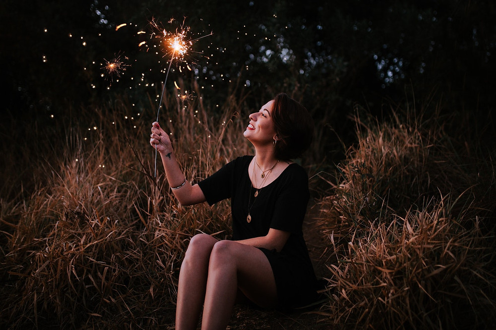 a woman holding a sparkler after dark