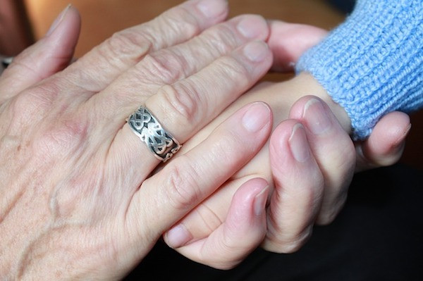 older woman holding child's had