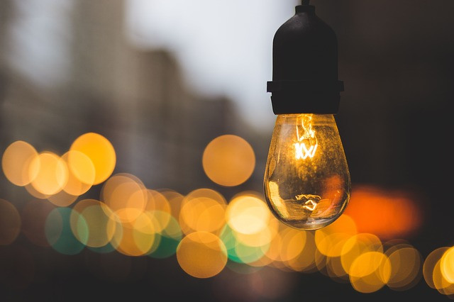 single lighted bulb with lights in background