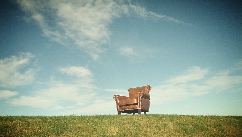 a chair under a broad blue sky