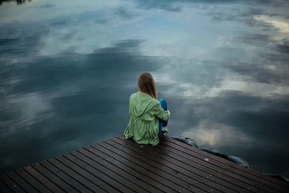 woman sitting contemplatively on a dock