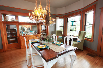 The dining room with new paint, a custom chandelier we found in a repurposed furniture store, and distressed furniture.