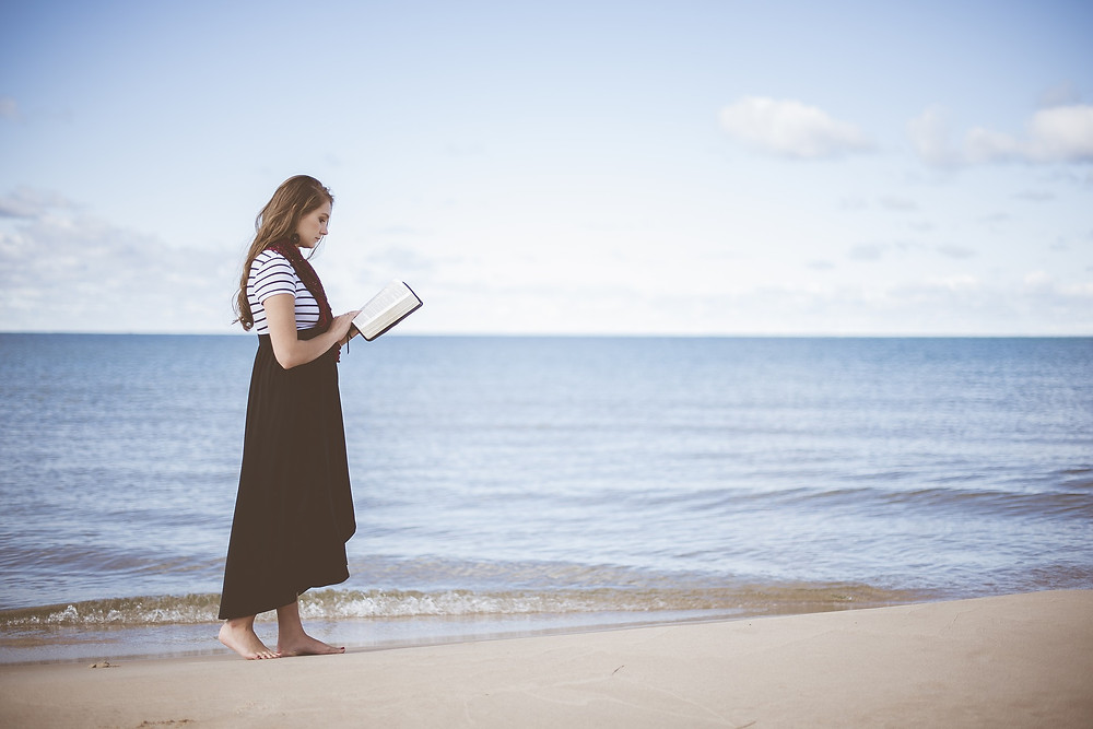 woman reading Bible at the ocean