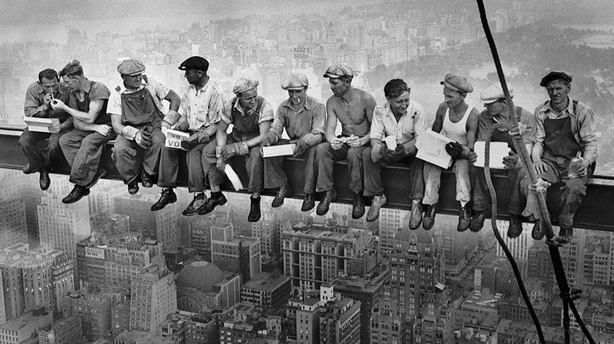 men eating on a girder