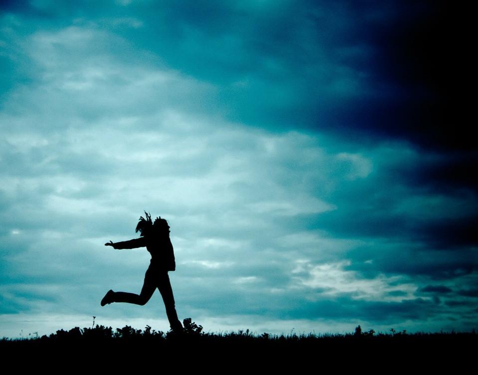 woman running under a dark sky
