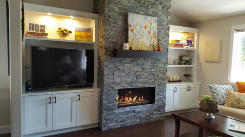 TA-DA! The new fireplace complete with leaping flames, beautiful gray green stack stone and a chunky mantle.