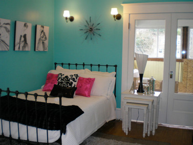 This is the re-decorated bedroom by designer Paula Kotchik of PMK Interiors for the Holiday Home Tour. You can see the unfinished sleeping porch through the French doors.