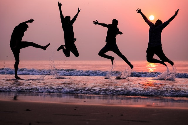 people jumping in ocean at sunset