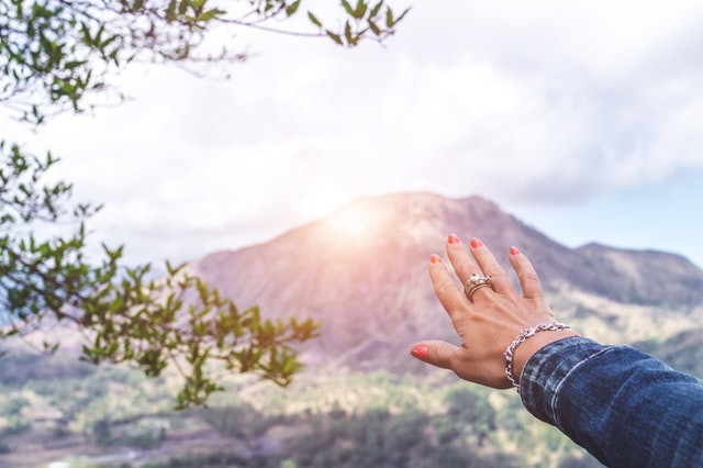 woman's hand reaching to sunlight on a mountain