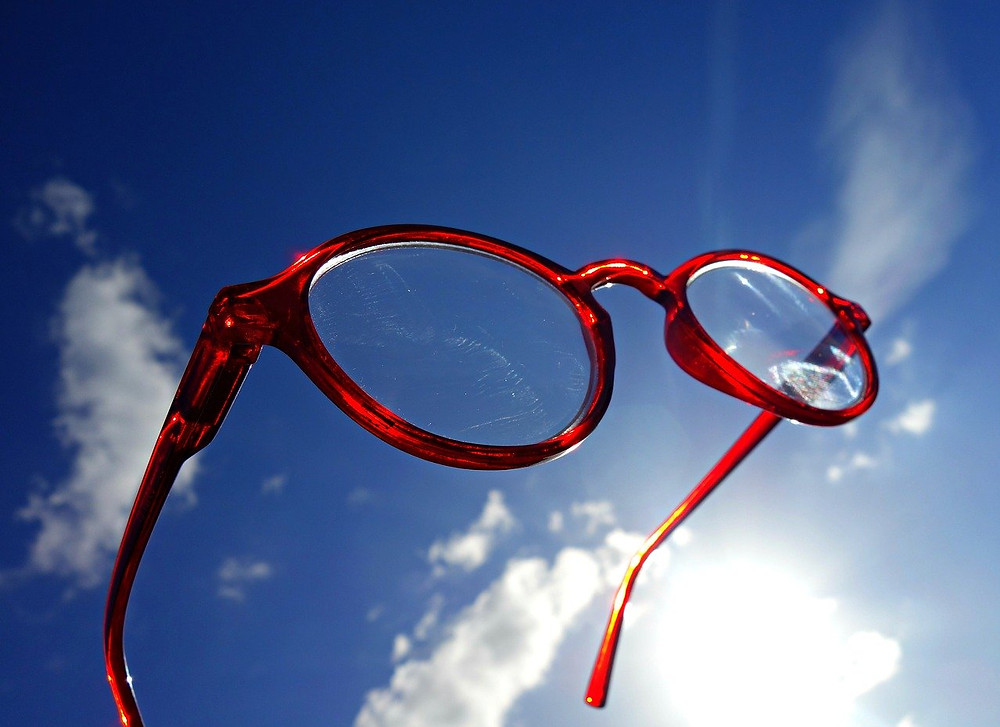 red glasses looking into blue sky