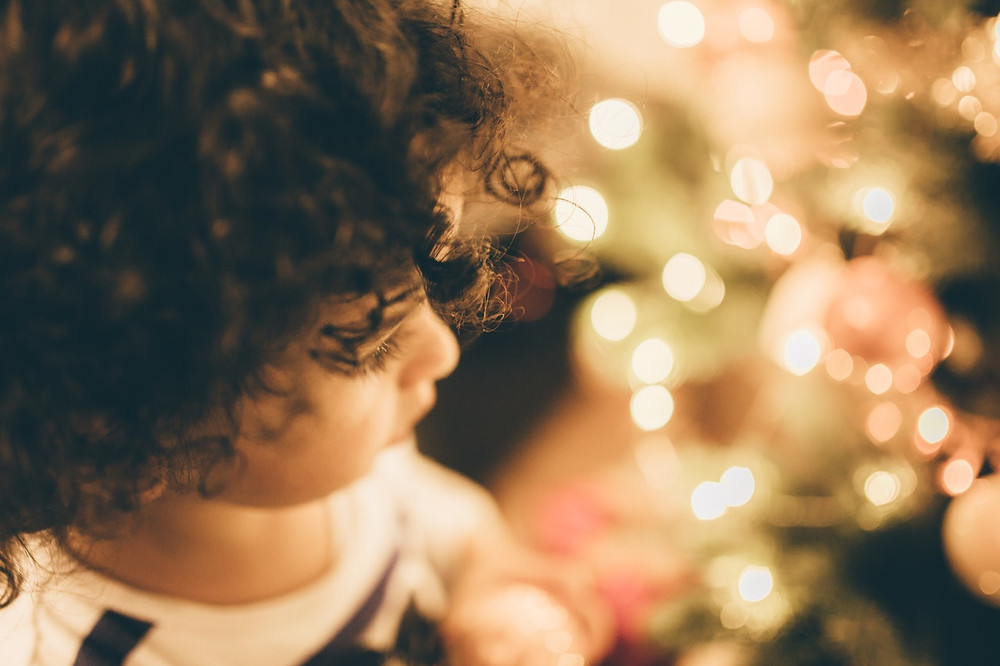 a small girl looks at tree lights