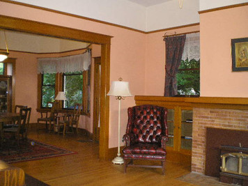 The before photo of the living room with the brick fireplace and the outdated paint color