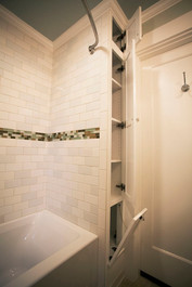We turned the wasted space at the end of the tub (and some borrowed space from the hall closet) into a linen closet with a laundry chute down to the basement.