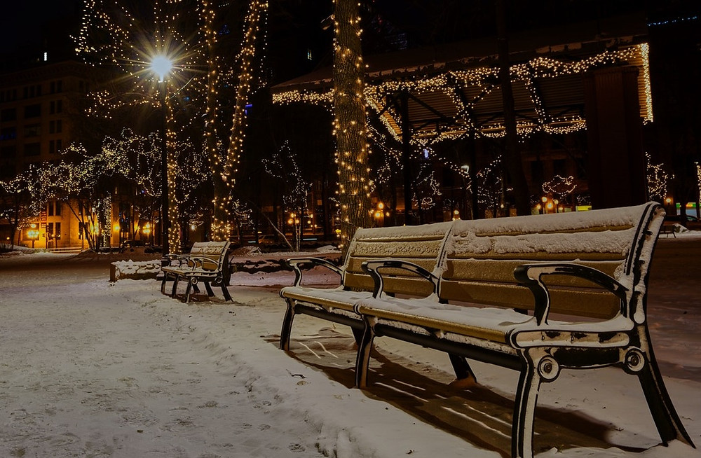 a snow covered bench on a lighted street