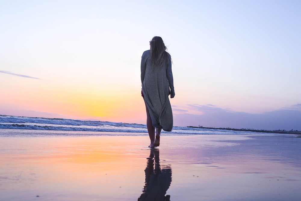 woman walking on the beach with a pastel sunsert