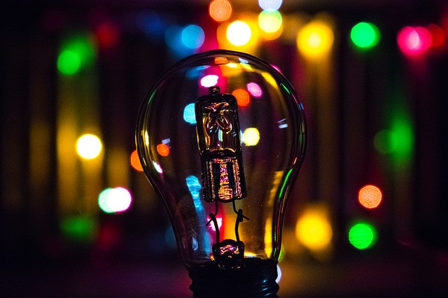light bulb with background of colored lights