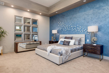 A Venetian plastered wall and silver gray accents decorated the master bedroom